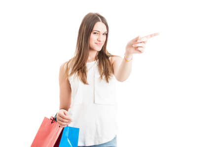 Beautiful young shopaholic indicate left direction with her finger or pointing left isolated on white background