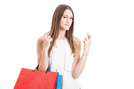 finger crossed: Attractive smiling female at shopping holding finger crossed as lucky or wish concept isolated on white background Stock Photo