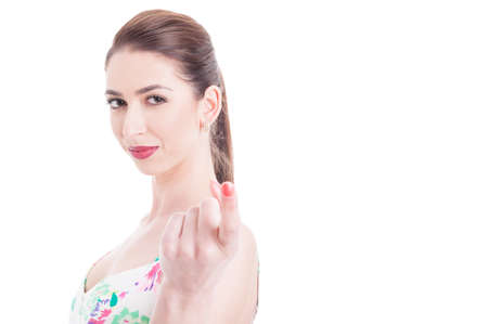 Beautiful woman looking at camera and doing appealing gesture with index finger isolated on white background with copy space area Фото со стока