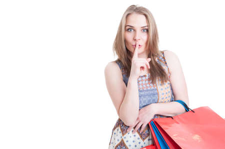 shush: Silent concept with stylish beautiful woman doing shush gesture and holding shopping bags isolated on white