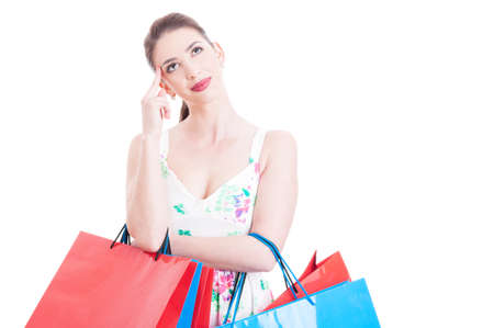 feeling up: Woman shopper holding gift bags looking up smiling and feeling pensive isolated on white background with advertising area Stock Photo