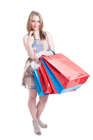 finger crossed: Young shopper with gift bags holding finger crossed looking hopeful and smiling isolated on white background
