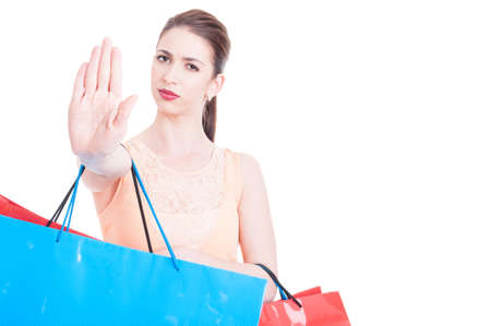 refusal: Woman carrying shopping bags making stop or refusal gesture white background with advertising area
