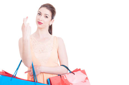 crossed fingers: Beautiful woman at shopping making crossed fingers sign as good luck gesture isolated on white background with copy space
