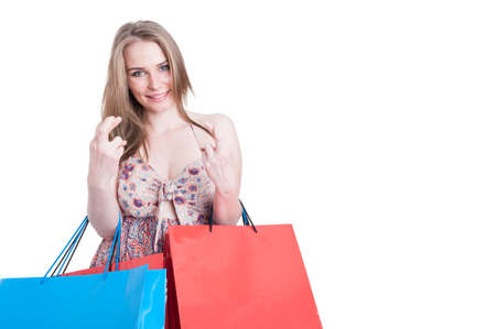 finger crossed: Smiling shopper woman with shopping bags holding finger crossed and wishing for good luck isolated on white with copy space