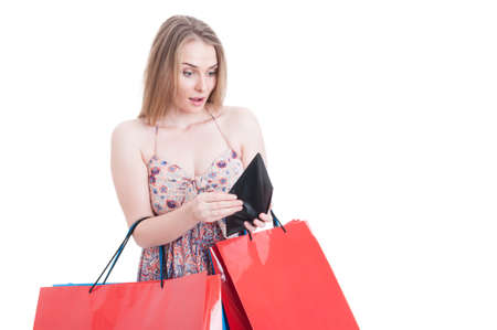overspending: Surprised female shopper at shopping looking into her empty wallet as overspending and bankruptcy concept isolated on white with advertising area Stock Photo