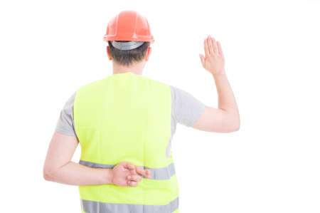 Young constructor taking oath with crossed fingers behind his back as dishonesty concept isolated on white background
