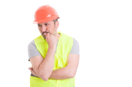 meditative: Meditative young builder with helmet and protection vest thinking to a plan isolated on white background with text area