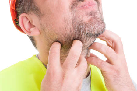irritation: Closeup of male builder scratching his beard with both hands as irritation concept isolated on white background