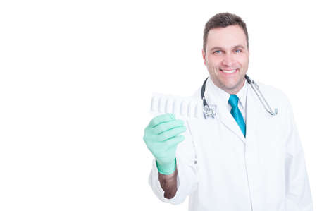 suppository: Male medic holding blister of suppositories and smiling isolated on white background with copy text advertising space
