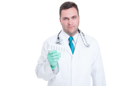 suppository: Male medic feeling uncomfortable about suppositories blister in hand isolated on white background