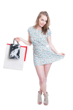 gift spending: Pretty young shopper woman in summer dress and modern high heels isolated on white studio background Stock Photo