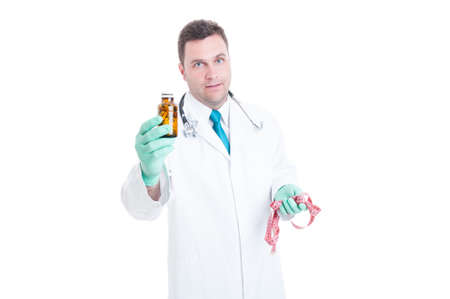 loosing: Male medic or nutritionist offering pills for loosing weight holding a body ruler isolated on white background Stock Photo