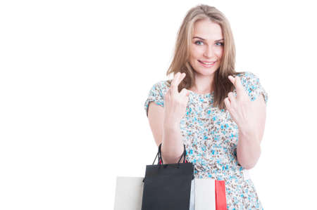 superstition: Confident young smiling shopaholic holding fingers crossed as superstition concept isolated on white background with advertising or text area