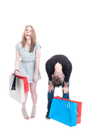 gift spending: Cheerful shopper female laughing of her tired boyfriend after a long day of shopping isolated on white with advertising area Stock Photo