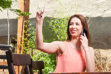 lady on phone: Pretty lady talking at phone and ordering on terrace outdoor