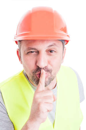 shush: Silence concept with handsome constructor in closeup doing a shush gesture isolated on white background Stock Photo
