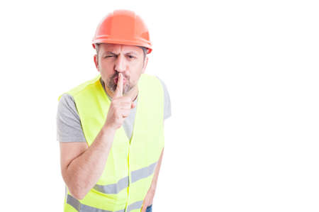 shush: Constructor doing a quiet or shush gesture isolated on white background with advertising area