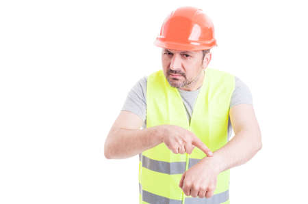 getting late: Angry male engineer pointing at his wrist as getting late or deadline concept isolated on white background with copyspace Stock Photo