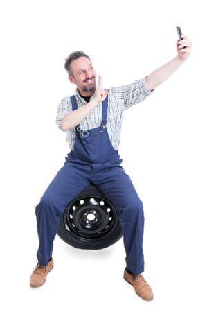 Joyful mechanic sitting on tire and taking selfie with smartphone and doing victory sign isolated on white background
