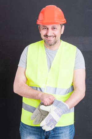constructor: Happy attractive constructor getting ready for work and putting gloves on isolated on black background