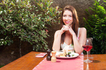 wafting: Beautiful lady smiling outside on terrace and wafting to have lunch and wine with copy text space
