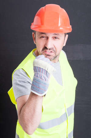 irritated: Angry male constructor in protection equipment showing fist and looking irritated against black background