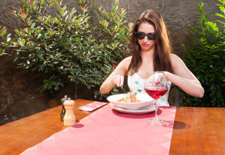eating area: Young lady eating lunch and wine outside on terrace on sunny day with copy advertising area Stock Photo