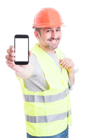 Smiling attractive builder holding modern smartphone with blank screen and copyspace isolated on white studio background Standard-Bild