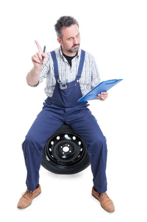 refusal: Young serious worker with checklist making refusal gesture and sitting on wheel isolated on white background Stock Photo