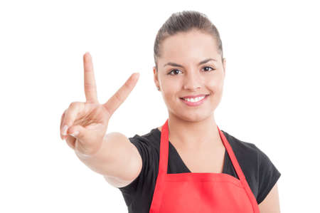 merchandiser: Portrait of smiling attractive female merchandiser on supermarket showing victory sign isolated on white background