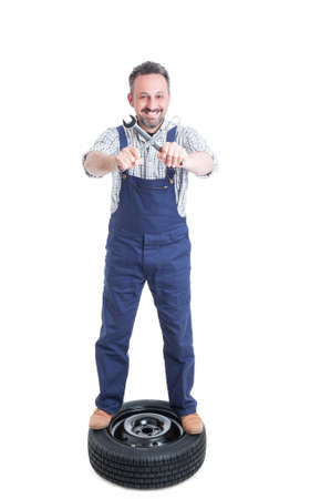 pneumatic tyres: Joyful repairman on tire holding crossed wrench and smiling isolated on white background