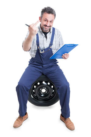insulting: Attractive mechanic on tire showing middle finger as insulting and obscene gesture concept isolated on white background