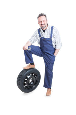 pneumatic tyres: Confident young engineer standing near car wheel with spanner in his hand isolated on white background