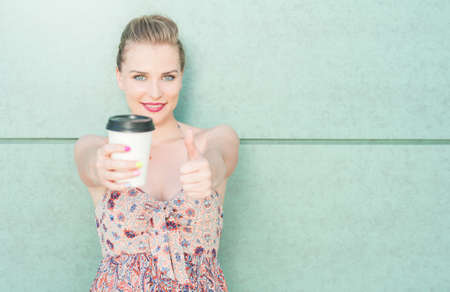 glamour girl: Pretty girl showing coffee mug and making like or approval gesture on green wall background with copy text space