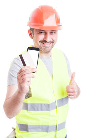 secured payment: Secured payment concept with builder holding debit card and smartphone while showing like gesture isolated on white