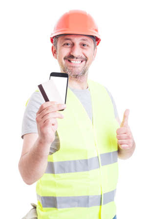 secured payment: Cheerful builder paying with credit card for construction services and thumb up isolated on white background Stock Photo