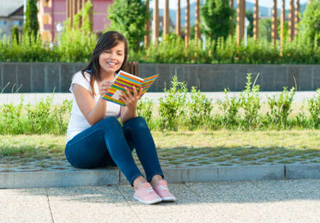 girl sitting down: Pretty girl sitting down in park and reading from notebook or diary with copy text space