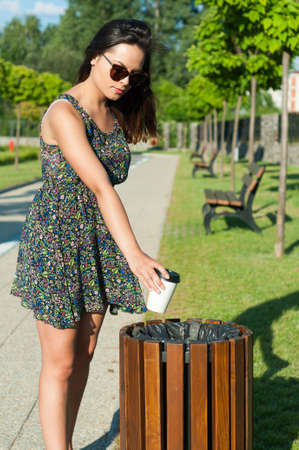 trash the dress: Beautiful girl wearing summer dress throwing paper cup on trash in park Stock Photo