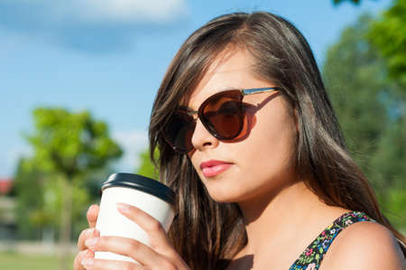 Girl close-up holding and looking at takeaway coffee wearing sunglasses on sunny day outside with copy text space