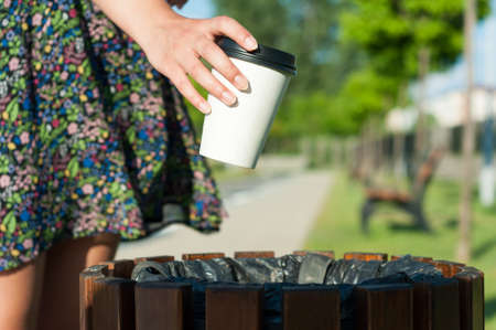 trash the dress: Close-up female hand throwing paper cup on trash bin outside in park with copy text space area Stock Photo