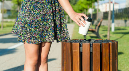 trash the dress: Young female hand throwing paper cup on trash bin outside  in park