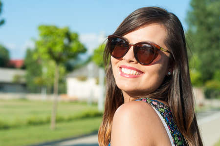 Close-up of smiling attractive girl posing outside in park on sunny day wearing sunglasses with copy text space