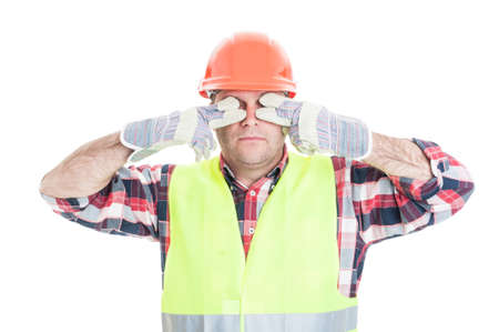 Male builder making the see no evil gesture by covering his eyes isolated on white background Stock Photo