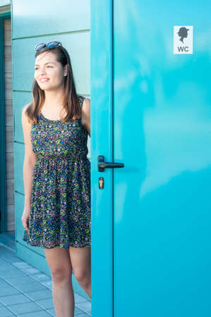 Girl smiling and using public restroom outside with copy text space Stock Photo