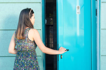 Young woman entering public toilet outside in park with copy text space