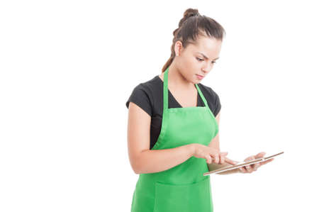 Young supermarket worker searching something on tablet or checking sales isolated on white background with advertising area
