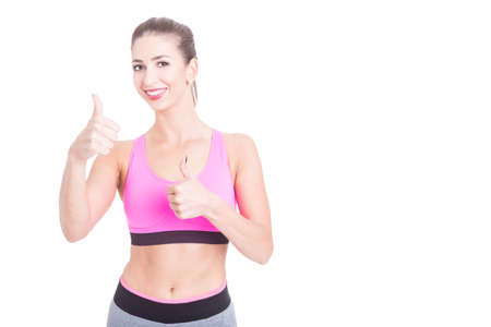 Female fitness trainer showing okay gesture and smiling isolated on white with copy text advertising area