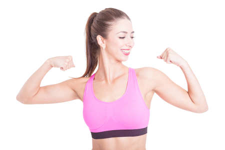 Fit girl or fitness trainer smiling and showing her biceps isolated on white background Stock Photo