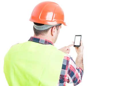 Backview van mannelijke ingenieur die mobiele telefoon met een leeg scherm en copyspace op wit wordt geïsoleerd